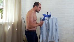 The man is having fun, stroking his shirt and humming at home