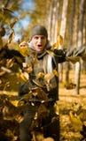 Man having fun throwing autumn leaves . Stock Image