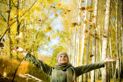 Man having fun throwing up piles of leaves . Young man having fun throwing up piles of autumn leaves Stock Photos