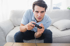 Man having fun with video games while he is sat on a sofa Stock Photography