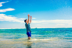 Man having fun in water on the beach Stock Photo