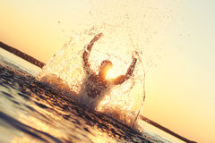 Man having fun in the water at sunset. Silhouette at sunset stock photography