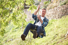 Man Having Fun On Woodland Swing Royalty Free Stock Image