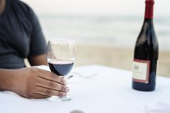 Man having a glass of wine by the sea royalty free stock images