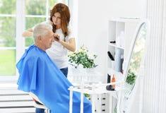 Man having a haircut  from  hairdresser Stock Photos
