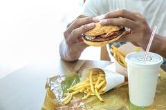 Man having a hamburger in a fast food restaurant Royalty Free Stock Photography