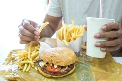 Man having a hamburger in a fast food restaurant Royalty Free Stock Images