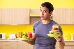 The man having hard choice between healthy and unhealthy food royalty free stock photography