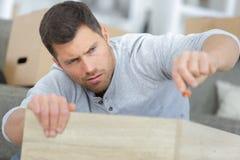 Man having hard time assembling furniture Stock Photo