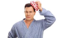 Man having a headache and holding an ice pack Stock Photography