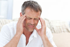 Man having a headache at home Stock Photo