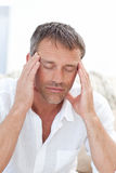 Man having a headache at home Stock Photos