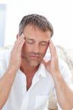 Man having a headache at home Stock Photos