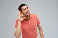 Man having hearing problem listening to something. Gesture and people concept - latin man having hearing problem listening to something Royalty Free Stock Photos