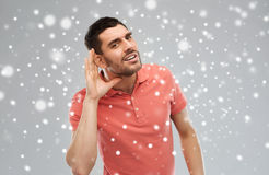 Man having hearing problem listening to something. Gesture, winter, christmas and people concept - man having hearing problem listening to something over snow on Stock Photos