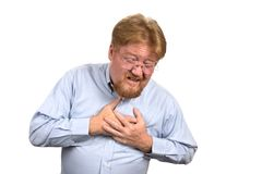 Man Having Heart Attack. Mature man in his mid fifties clutches his chest as he reacts to heart attack pains Stock Image
