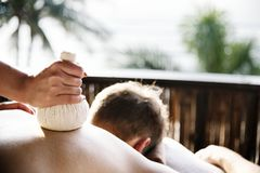 Man having an herbal compress massage at a spa Stock Image