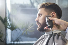 Man having his beard trimmed stock photography
