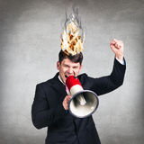 Man having his brain on fire because of stress. On a gray background Stock Photo