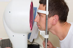 Man having his eyes examined by an eye elderly Royalty Free Stock Images