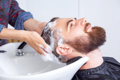 Man having his hair washed in a hairdressing salon. Close-up of a young caucasian men having his hair washed in a hairdressing salon stock image
