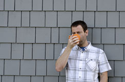 Man having a hot beverage outside. Stock Image