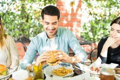 Man Having Joy Eating Burger. Delighted men holding mouthwatering burger during reunion with friends royalty free stock photo