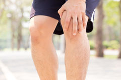 Man having knee pain while exercising Royalty Free Stock Images