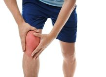 Man having knee problems on white background. Closeup stock images