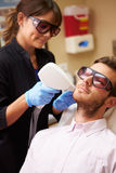 Man Having Laser Treatment At Beauty Clinic. By Beautician Wearing Safety Goggles royalty free stock images