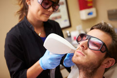 Man Having Laser Treatment At Beauty Clinic. Wearing Protective Goggles Sitting Down stock photography