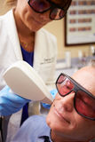 Man Having Laser Treatment At Beauty Clinic. Wearing Safety Goggles royalty free stock images