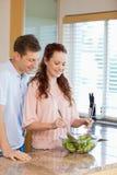 Man having a look at his girlfriends salad Royalty Free Stock Images