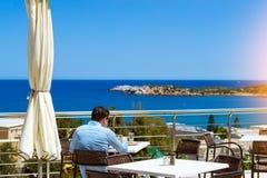 Man is having lunch on veranda of restaurant, hotel Atali Villag Royalty Free Stock Images