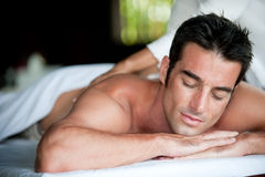 Man Having Massage. A good-looking man getting a back massage lying down Royalty Free Stock Photos