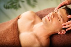 Man having massage in a spa. Handsome man having face massage in spa salon Royalty Free Stock Photography