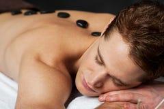 Man having massage at spa. Young man getting a hot stone massage at spa Royalty Free Stock Photo