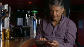 Man having a pint at  the bar using tablet. In high quality 4k format stock video footage