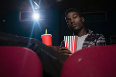 Man having popcorn and cold drink while watching movie Stock Photography