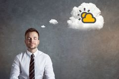 Man having positive thoughts. Man with eyes closed and a light smile. A thought bubble is depicting a shining sun behind a cloud Stock Image