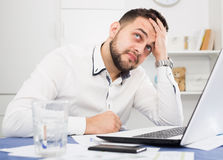 Man having problem in office. Young male worker having problem in project in office Royalty Free Stock Image