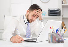 Man having problem in office. Young male worker having problem in project in office Stock Photos