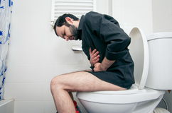 Man having problems in  toilet Stock Images