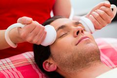 Man having face massage in wellness spa stock photography