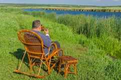 Man having rest on a riverside Royalty Free Stock Images