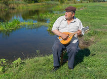 Man having rest on a riverside sitting on a wicker stool, singing and playing mandolin Stock Image