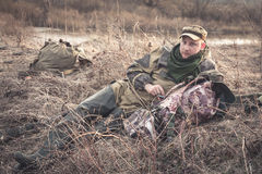 Man having a rest at sunset in rural field with backpack during hunting season Royalty Free Stock Images