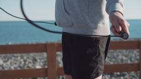 Rope jumping workout. Man having rope jumping training on waterfront. Regular sports activities to keep fit and healthy stock footage