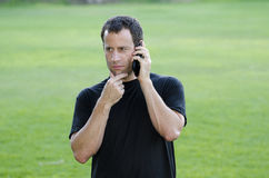 Man having a serious phone call. Outdoors with hand rubbing his chin Stock Images