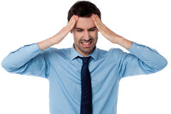 Man having severe headache. Man suffering from headache wincing Royalty Free Stock Image